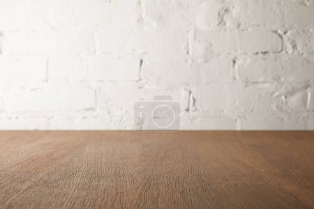 Photo for Brown wooden tabletop and white wall with bricks - Royalty Free Image