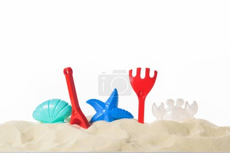 Photo for Plastic beach toys in sand isolated on white - Royalty Free Image