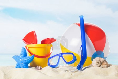 Diving mask with beach ball and toys in sand on blue sky background