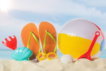 Flip flops with beach ball and toys in sand on blue sky background