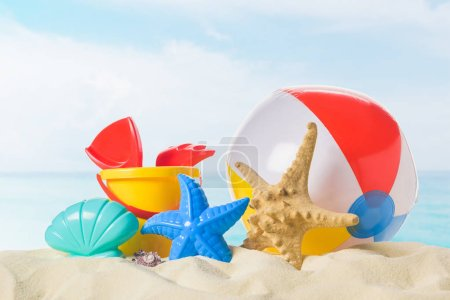 Beach ball and toys in sand on blue sky background