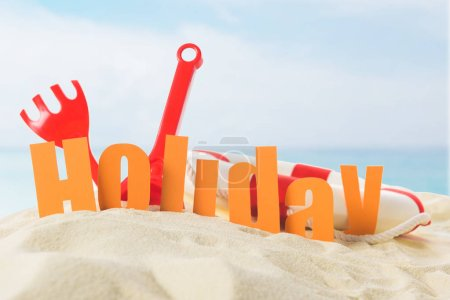 Beach toys and Holiday inscription in sand on blue sky background