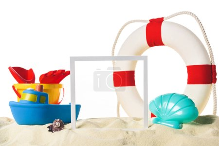 Beach toys with life ring and frame in sand isolated on white