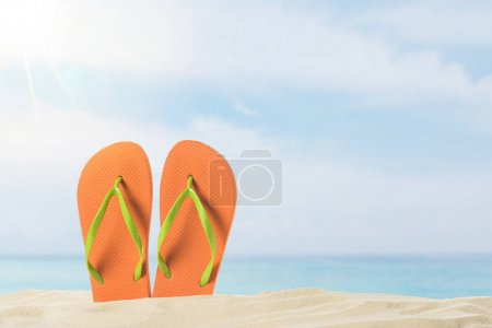Photo for Pair of flip flops in sand on blue sky background - Royalty Free Image