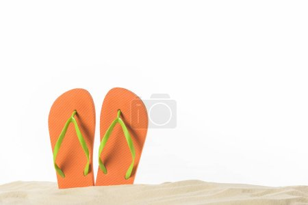 Photo for Pair of flip flops in sand isolated on white - Royalty Free Image