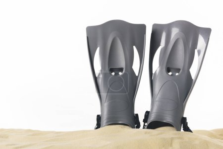 Black flippers in sand isolated on white