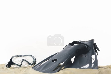 Mask and flippers in sand isolated on white