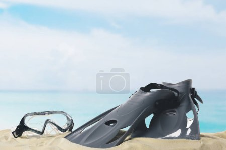 Mask and flippers in sand on blue sky background