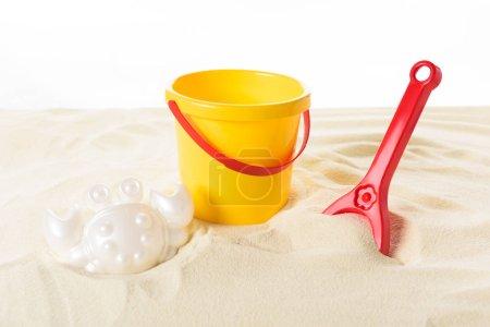 Photo pour Seau et jouets en plastique dans le sable isolé sur blanc - image libre de droit