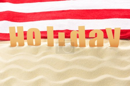 Photo for Holiday inscription in front of towel on sandy beach - Royalty Free Image