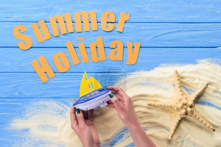 Woman holding toy boat by Summer holiday inscription on blue wooden background