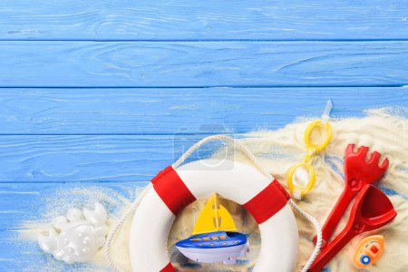 Life ring and toy boats on blue wooden background