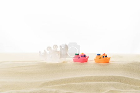 Photo for Toy boats and crab in sand isolated on white - Royalty Free Image