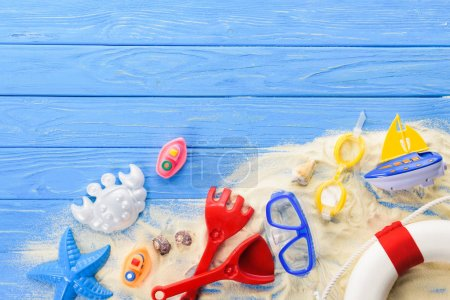 Photo for Diving mask and beach toys on blue wooden background - Royalty Free Image
