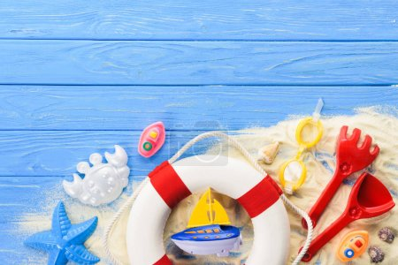 Photo for Life ring and beach toys on blue wooden background - Royalty Free Image