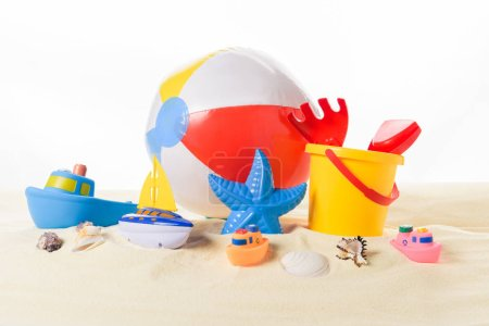 Beach ball and kid toys in sand isolated on white