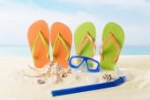 Flip flops and diving mask in sand on blue sky background