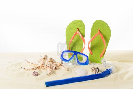 Flip flops and diving mask with seashells in sand isolated on white
