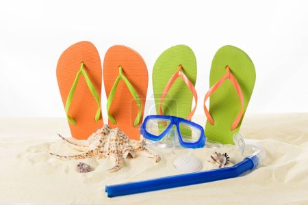 Photo for Flip flops and diving mask in sand isolated on white - Royalty Free Image