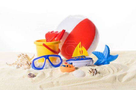 Beach ball and toys in sand isolated on white