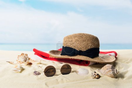 Straw hat and sunglasses with seashells in sand on blue sky background