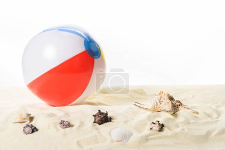 Beach ball with seashells in sand isolated on white