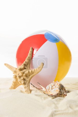 Beach ball and starfish in sand isolated on white