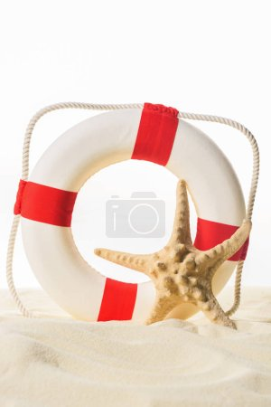 Life ring and starfish in sand isolated on white