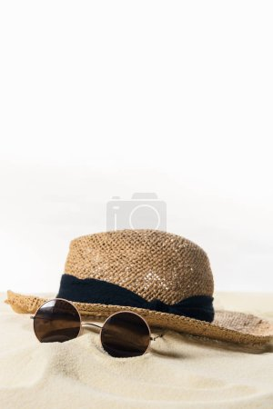 Straw hat and sunglasses in sand isolated on white