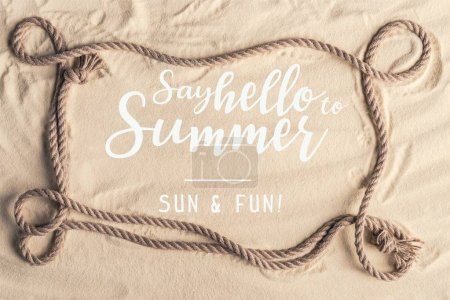 "Frame of ship rope on sandy beach with ""say hello to summer"" lettering"