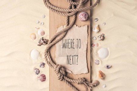 "Summer travel template with seashells and rope on wooden pier on light sand with ""where to next?"" lettering"