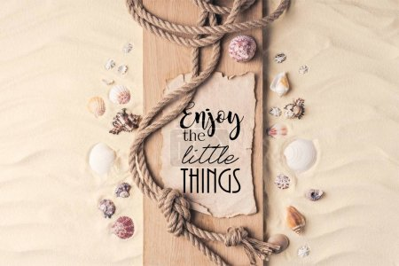 "Summer travel template with seashells and rope on wooden pier on light sand with ""enjoy the little things"" inspection"