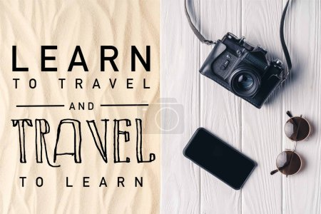 "Smartphone with camera and sunglasses on pier on light sand with ""learn to travel and travel to learn"" lettering"