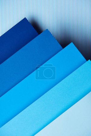 Paper sheets in blue tones on striped background