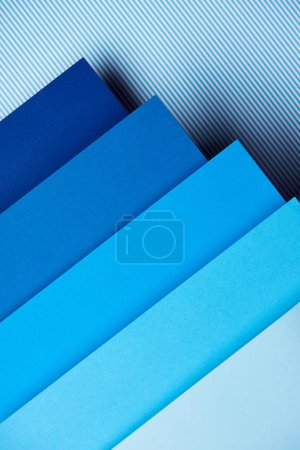 Paper in blue tones on striped background