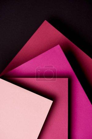 Hojas de papel en tonos rosados sobre fondo negro