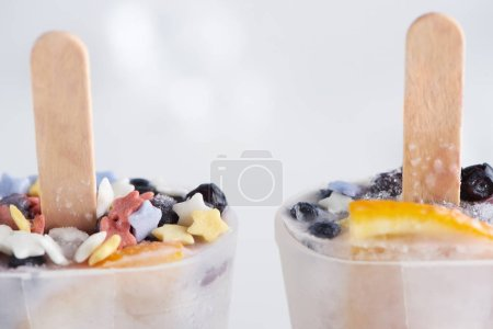 close-up view of sweet homemade ice cream with sticks in containers on grey