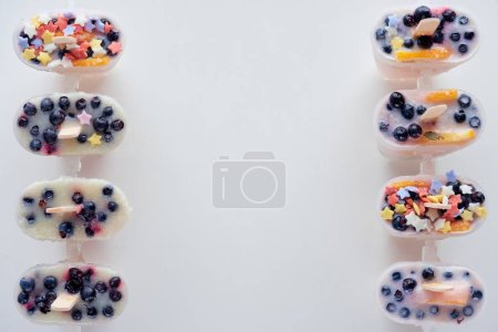 top view of cold sweet homemade popsicles with fruits and berries on grey background