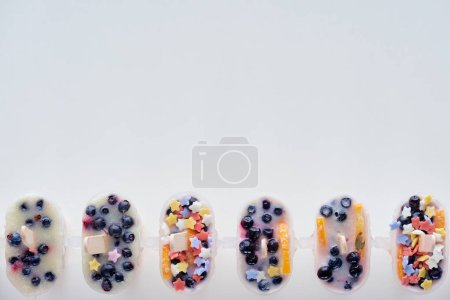 top view of cold homemade ice cream with fruits and berries on grey background