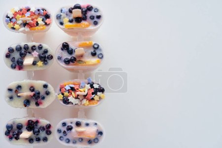 top view of cold homemade ice cream with fruits and berries on grey