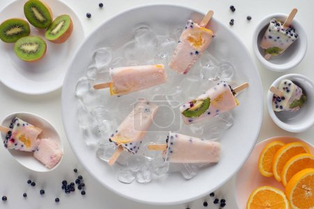 top view of delicious homemade popsicles with ice cubes and sliced fruits on grey