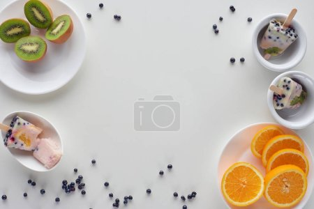 top view of tasty homemade popsicles in bowls, slices of orange and kiwi on plates and berries on grey background