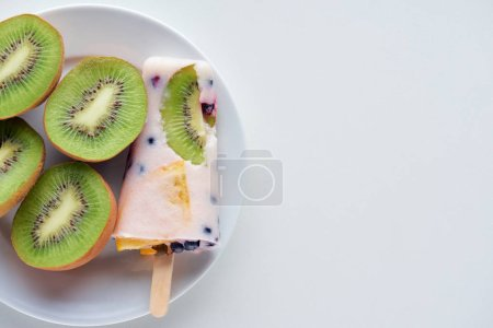 top view of delicious homemade popsicle with berries and slices of kiwi on plate on grey