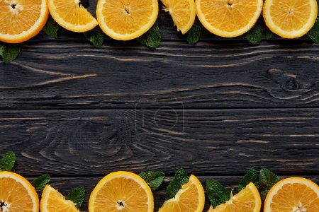 Photo for Top view of fresh orange slices and mint leaves on dark wooden table top - Royalty Free Image