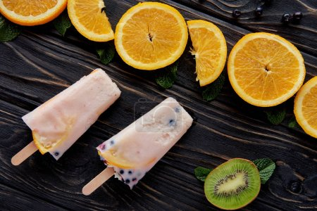 top view of delicious homemade ice cream with fruits and mint on wooden surface