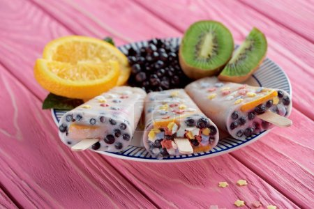 sweet homemade ice cream with fresh fruits and berries on plate on pink wooden table