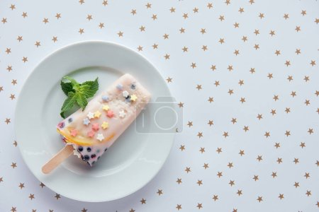 top view of delicious fruity popsicle with mint leaves on plate and beautiful golden stars on grey