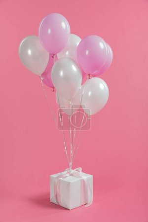 Bunch of balloons tied on gift box on pink background