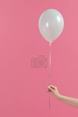 Cropped view of woman holding single white balloon isolated on pink