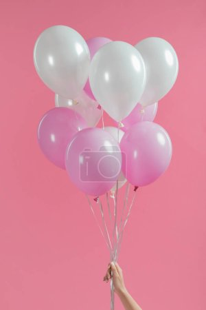 Cropped view of holding pink and white balloons in girl hand isolated on pink